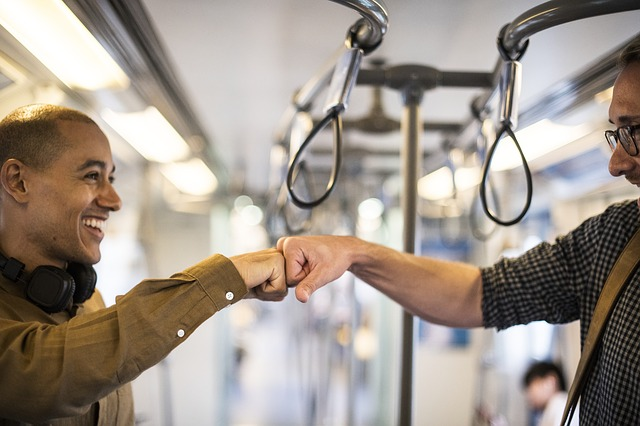 People fistbumping on public transportation